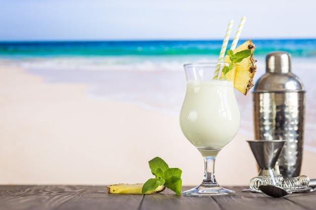 Kalter pina colada cocktail in einem glas am strand mit seestückhintergrund