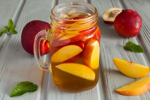 Kalter tee mit pfirsich und früchten auf der grauen holzoberfläche