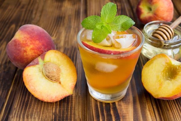 Kalter tee mit pfirsichen im glas auf dem braunen holztisch