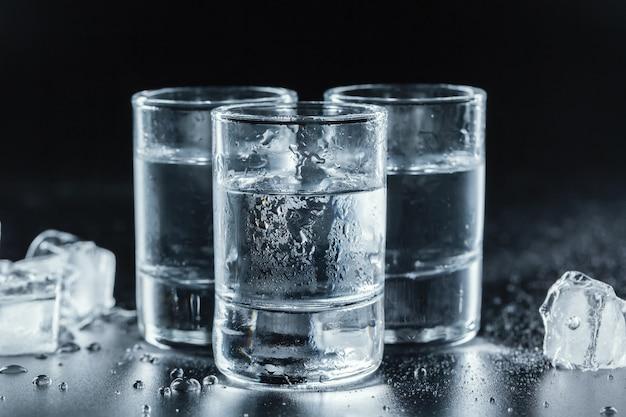 Kalter wodka in den schnapsgläsern auf schwarzem