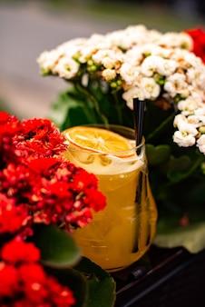 Kalter zitruscocktail mit orangensaft und limettenminze und eis in einem glas an der bar