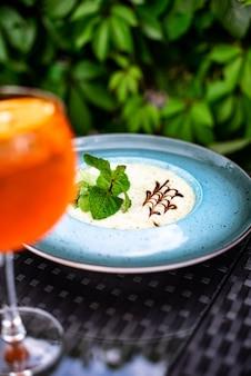 Kalter zitruscocktail mit orangensaft und minze und eis in einem glas mit tropfen. buntes alkoholisches cocktailgetränk an der bar.