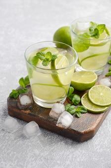 Kaltes auffrischungssommergetränk mit kalk und minze in einem glas auf einem grauen beton oder einem stein.