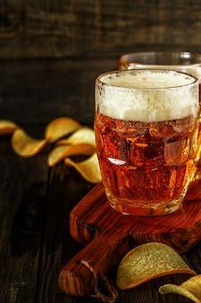 Kaltes bier im glas mit pommes auf einem dunklen tisch.