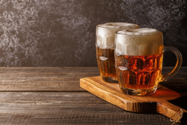 Kaltes bier in glas mit pommes auf einer dunklen oberfläche