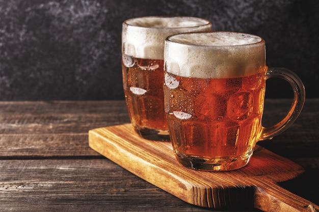 Kaltes bier in glas pints auf einem holzbrett