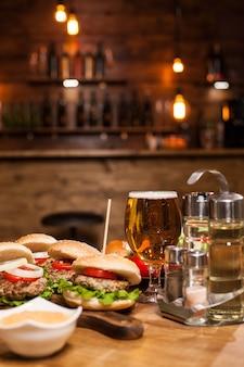 Kaltes bier mit klassischen burgern auf einem holztisch im restaurant. leckeres essen.