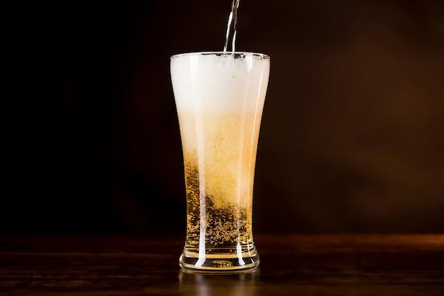 Kaltes bier wird mit schaumigem schaum darüber in das glas gegossen