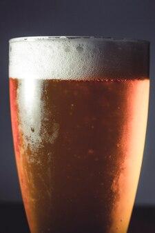 Kaltes bierglas auf einem dunklen hintergrund auf holztisch