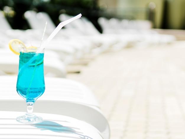 Kaltes blaues cocktail mit zitrone auf sonnenruhesessel