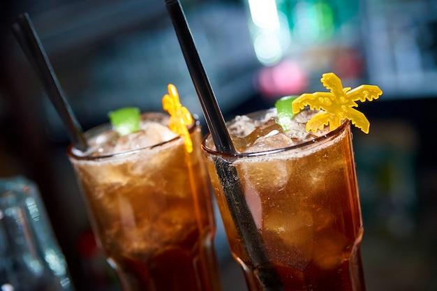 Kaltes cocktail auf einer dunkelheit verwischte hintergrund mit bokeh.