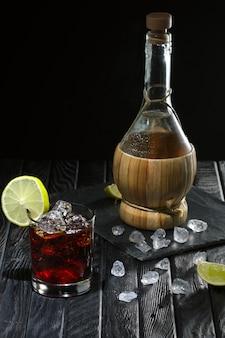 Kaltes cocktail mit wodka, limette und kaffeelikör und der flasche