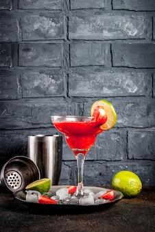 Kaltes erdbeer-margarita-cocktail mit eis, limette und frischen beeren im margarita-glas