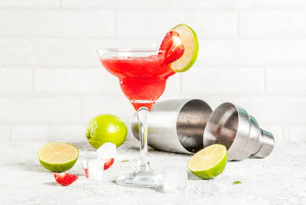 Kaltes erdbeer-margarita-cocktail mit eis, limette und frischen beeren