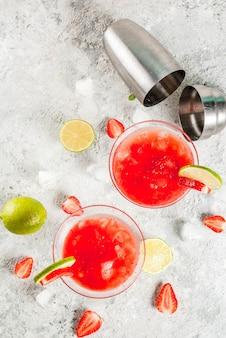 Kaltes erdbeer-margarita-cocktail mit eiskalk und frischen beeren im hellgrauen glashintergrund der margarita