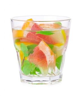 Kaltes getränk mit verschiedenen zitrusfrüchten und kräutern in gläsern. cocktail