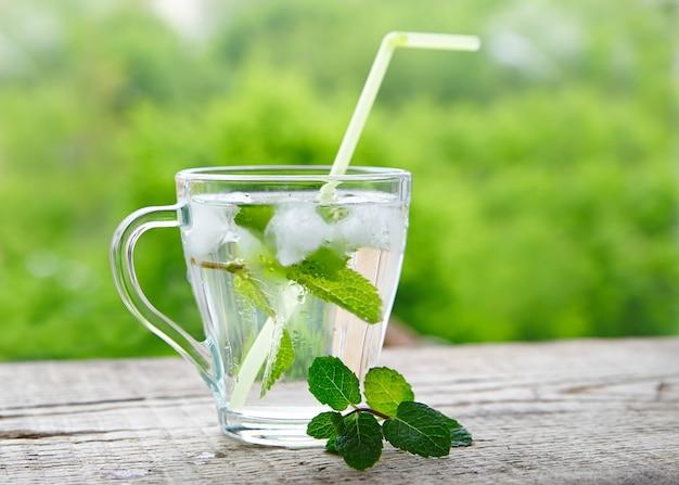Kaltes getränk mit zitrone und minze in einem glas mit strohhalmen
