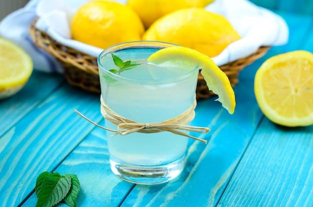 Kaltes glas limonade mit eis, zitrone und gignger auf buntem türkisblau malte woo