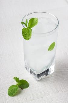 Kaltes glas trinkwasser mit eis und minze
