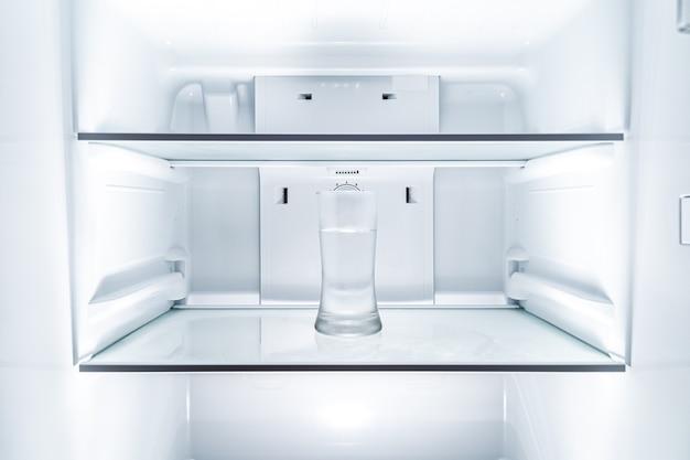 Kaltes glas wasser im sauberen kühlschrank