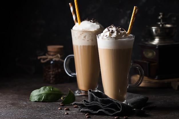 Kaltes kaffeegetränk frappe oder frappuccino mit schlagsahne und schokoladenstückchen, mit strohhalmen über dunkler oberfläche