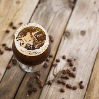 Kaltes kaffeegetränk mit eis auf hölzernem hintergrund
