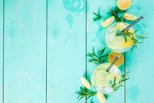 Kaltes limonaden- oder alkoholwodkacocktail mit zitrone und rosmarin, auf hellblauer tabelle, draufsicht