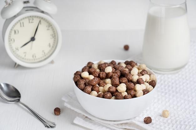 Kaltes müsli in einer schüssel mit löffel und glas milch zum frühstück auf dem tisch