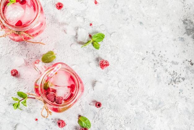Kaltes sommergetränk, himbeersangria, limonade oder mojito mit frischer himbeere und sirup, tadellose blätter, auf grauer stein-copyspace draufsicht
