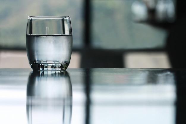Kaltes trinkwasserglas auf tabelle