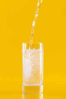 Kaltes wasser aus einer flasche in ein glas gießen