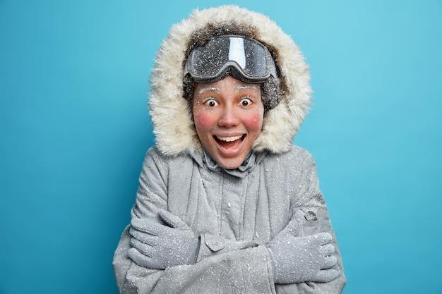 Kaltes winterwetter. aufgeregte fröhliche ethnische junge frau mit rotem gefrorenem gesicht umarmt sich, um sich während des frostigen tages zu wärmen, trägt thermojacke und snowboardbrille reagiert auf etwas emotional