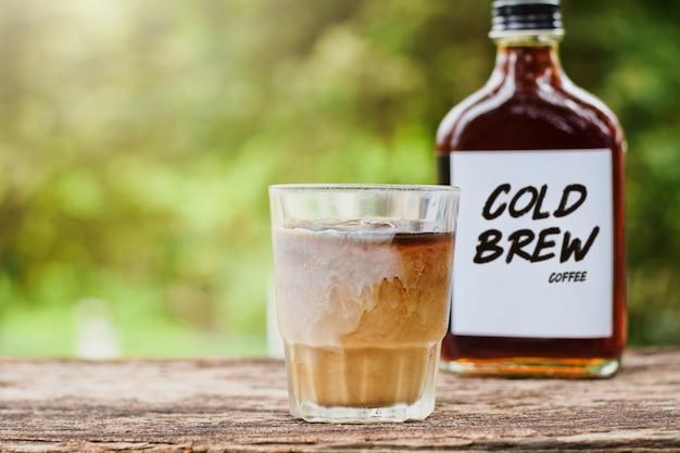 Kaltgebrühter kaffee mit milch auf einem tisch draußen mit kaltgebrühtem kaffee in einer glasflasche zum mitnehmen