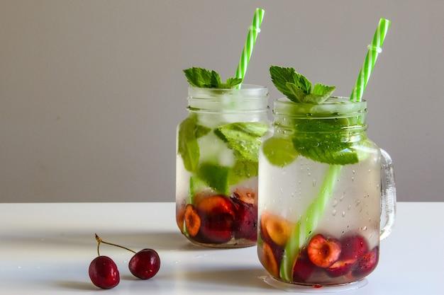 Kaltgetränke im kleinen glas kirschen und minzlimonade mojito-cocktail sommer-eisfrischgetränk
