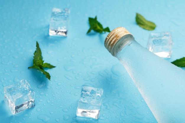Kaltwasserflasche, eiswürfel, tropfen und minzblätter