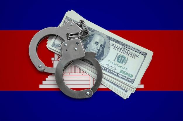 Kambodscha-flagge mit handschellen und einem bündel dollar. währungskorruption im land. finanzielle verbrechen