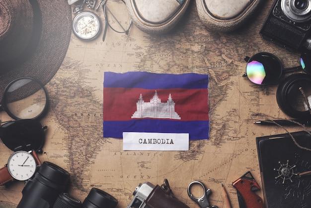 Kambodscha-flagge zwischen dem zubehör des reisenden auf alter weinlese-karte. obenliegender schuss
