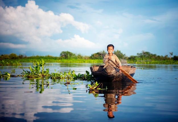 Kambodschanischer junge, der mit dem boot in sich hin- und herbewegendem dorf reist