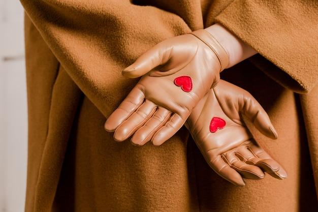 Kamelfarbene handschuhe mit roten herzen in der handfläche