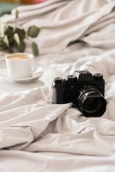 Kamera auf dem bett und kaffeetasse