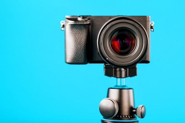 Kamera auf einem stativ, auf einem blauen. nehmen sie videos und fotos für ihr blog oder ihren bericht auf.