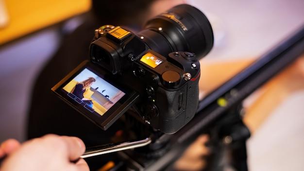 Kamera auf einem stativ, das ein junges mädchen mit tablette auf sofa schießt. von zu hause aus arbeiten