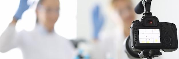 Kamera fängt weibliche chemiker-blogger ein, die in der nahaufnahme eines chemielabors winken