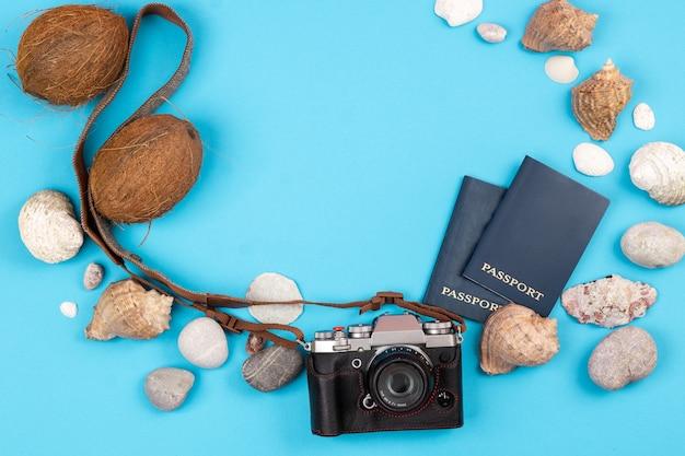 Kamera, kokosnüsse, muscheln und dokumente auf blauem hintergrund. hintergrund für den reisenden