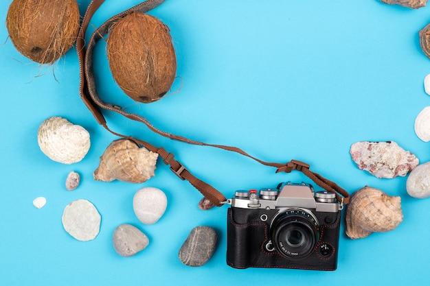 Kamera, kokosnüsse und muscheln auf blauem hintergrund. hintergrund für den reisenden