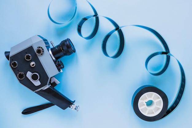 Kamera mit filmstreifen auf blau