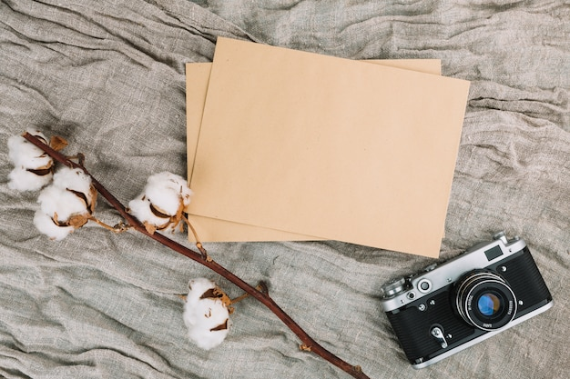 Kamera mit leerem papier und baumwollzweig
