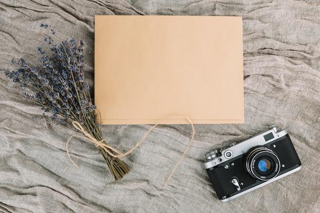 Kamera mit leerem papier und violettem blumenstrauß