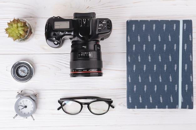 Kamera mit notizbuch auf holztisch