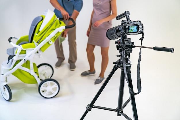 Kamera steht auf einem stativ auf dem hintergrund von mann und frau nahe grünem kinderwagen im studio